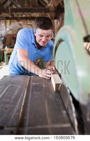 Male Carpenter Cutting Wood On Circular Saw