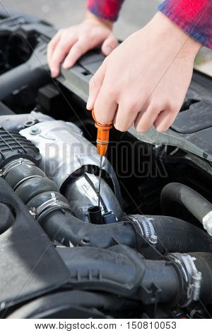 Checking Car Engine Oil Level Under Hood With Dipstick