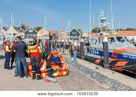 URK THE NETHERLANDS - SEP 24: Rescue workers showing a lifeboat and rescue equipment on September 24 2016 in the harbor of Urk the Netherlands