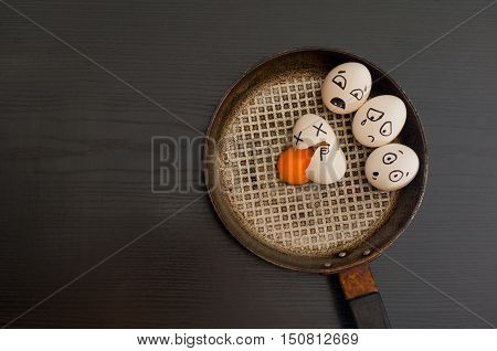 Eggs with the drawn emotions broken egg in the center of the pan black table