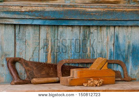 Planer hacksaw and a saw on an old wooden background chips