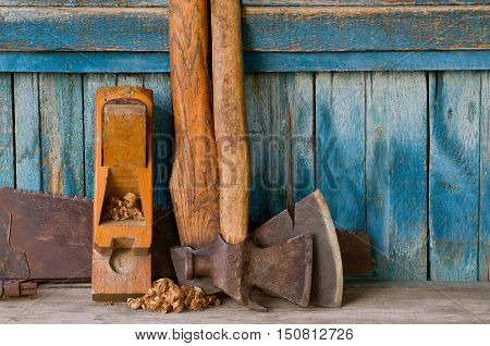 Axes planer shavings and saw the old blue wooden background