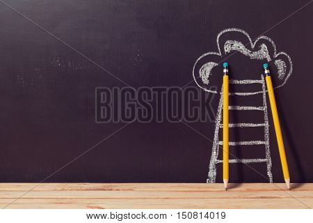 Success concept with pencils and ladder over chalkboard
