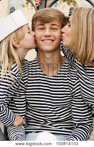 Beautiful young smiling family in sailor outfits. Beautiful young family mother and cute sister kissing young boy on the cheek. Happy family. Family concept.