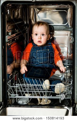 Cute baby sitting in empty dishwasher with tablet