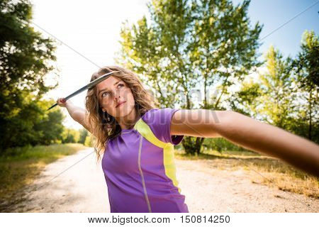 Wide angle view of a young woman throwing a javelin - outdoors on sunny day
