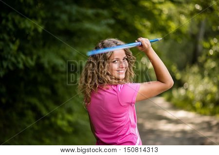 Close up of athletic young woman carrying a javelin over her shoulder