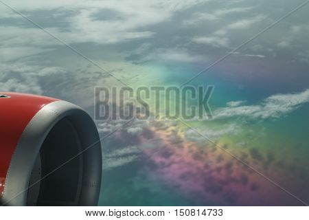 Great fragment of a view from on aircraft climbing above rainbow beautiful color clouds that bring attention