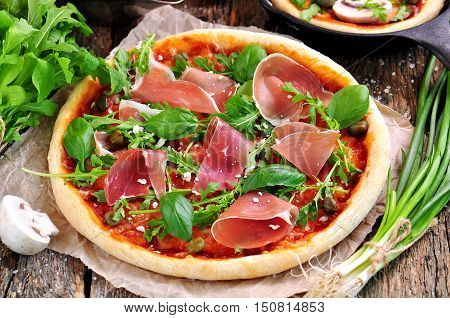 Homemade pizza with tomato sauce, mozzarella cheese, organic arugula, Parma ham, capers and parmesan cheese.