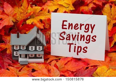 Home energy savings tips in the fall season Some fall leaves and gray house and greeting card with text Energy Savings Tips