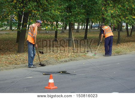 Smolensk, Russia - August 08, 2014: Janitors clean the garbage on the roadside
