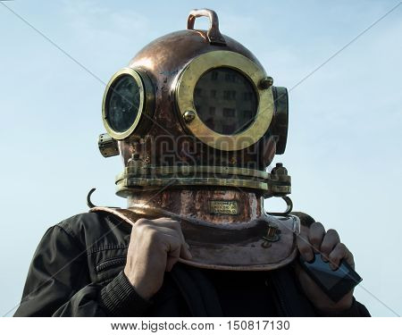 Man stands in his head to put on an old diving helmet