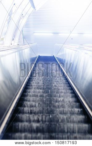 Escalator in a underground. Lights on a wall