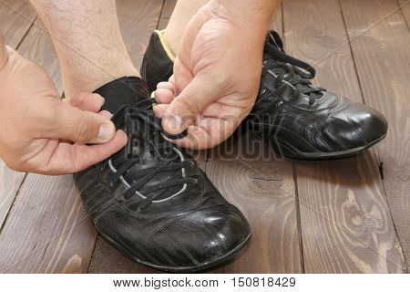 Tying Shoe laces a man sits on a wooden floor. the view from the top. Dark shoes on wooden background.