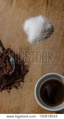 still life with a cup of coffee and a pile of coffee and one pile of white sugar