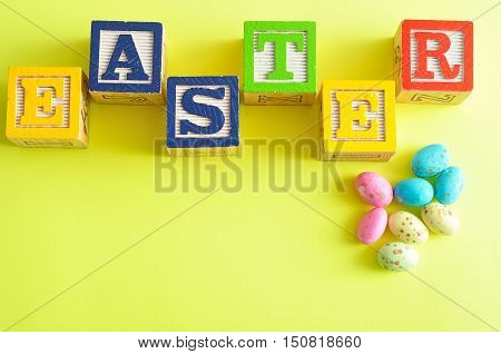 Easter spelled with colorful alphabet blocks isolated against a yellow background and small speckled eggs