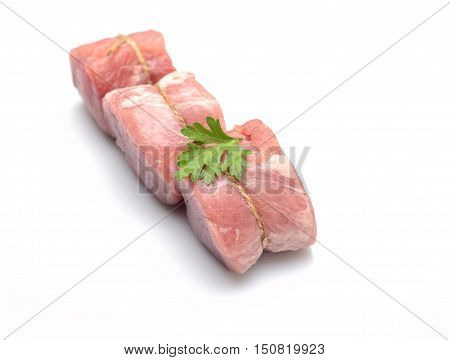 raw fillet medallions of young pork with parsley on a white background