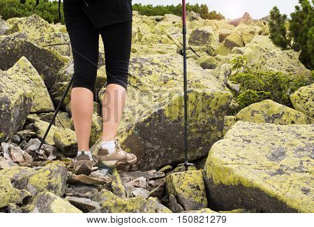 Woman hiking in mountains adventure and exercising. Legs and nordic walking poles in nature. Young fitness woman legs walking on mountains hike. Close-up of shoes and trekking poles on mountains