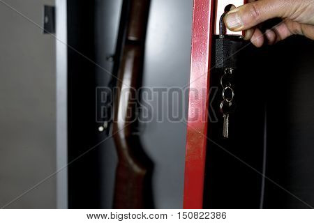 Human hand opening a metal safe with a gun inside, studio cropped shot