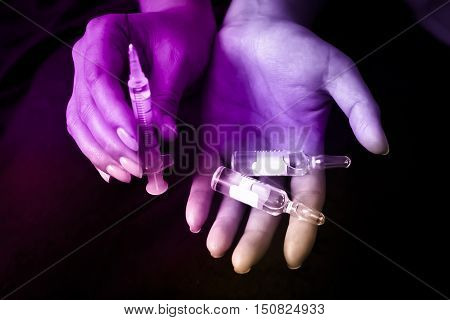 Stabbing drugs. the syringe and the hand enters injections, drugs, doping.