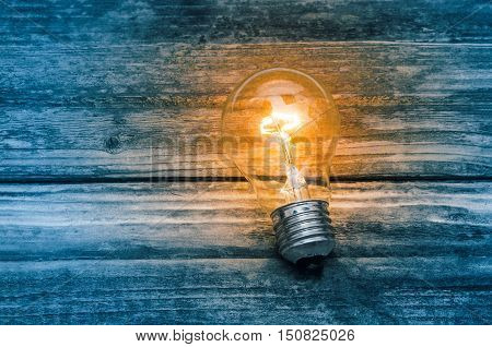 Glowing light bulb on grunge wooden background