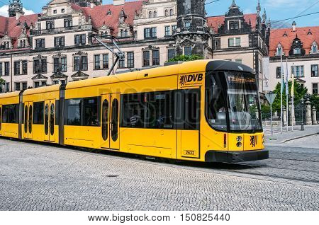 DRESDEN GERMANY- JUNE 20 2016: Yellow articulated tram SachsenTram at the city street
