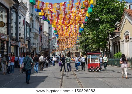 ISTANBUL TURKEY - JUNE 26 2015: People walking on Istiklal Street in Istanbul Turkey. It is the most famous street in Istanbul