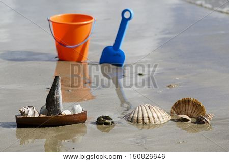Seashells bucket and spade on the beach during summer vacation.