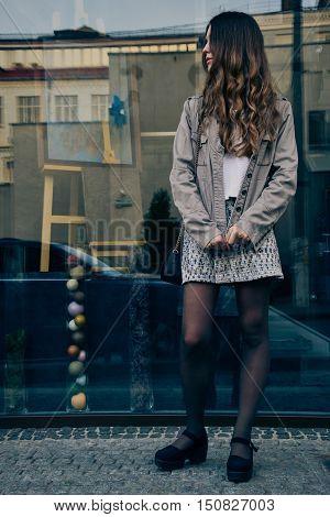 Stylish girl in skirt standing near glass shop window on city street