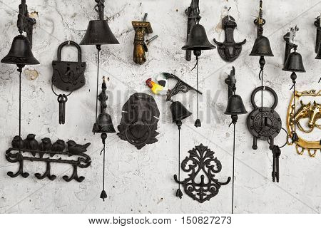 souvenirs on the wall: bells, locks, hangers, knockers