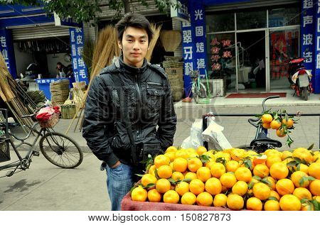 Pengzhou China - December 10 2009: Young Chinese man selling fresh local oranges from his bicycle cart at the Tian Fu outdoor market