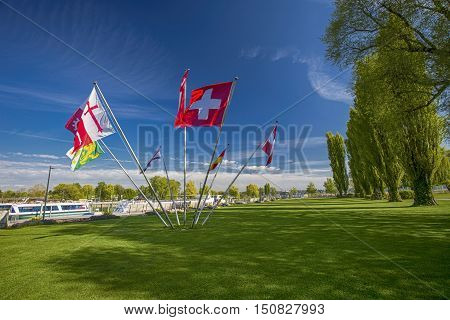 Swiss and cantonal flags in the centre of park in Kreuzlingen with the lake Constance in the background Switzerland.