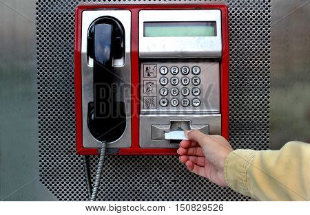 The girl puts the card into the phone on the main street of a large city