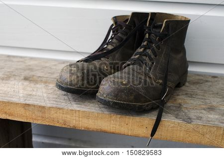 Dirty old working boots outside a house.