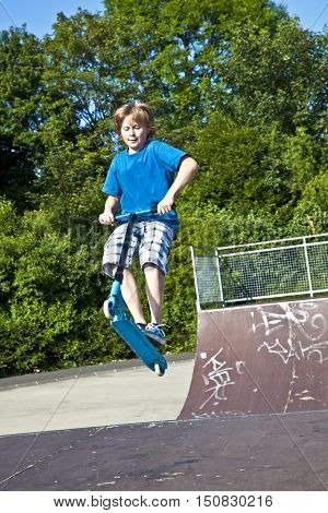 Young Boy Going Airborne With A Scooter