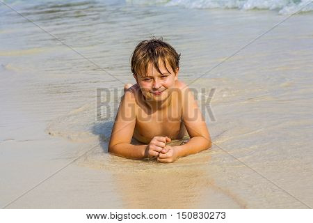 Boy Is Lying At The Beach And Enjoys The Water And Looking Self Confident And Happy