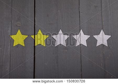 Two yellow ranking stars on black wooden background