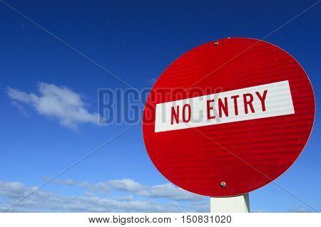 Do not enter - roadsign under cloudy blue sky.