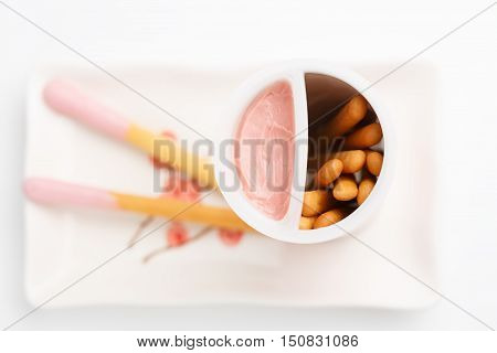 Biscuit cookie sticks with pink friut cream on rectangular plate with flower pattern isolated on white background