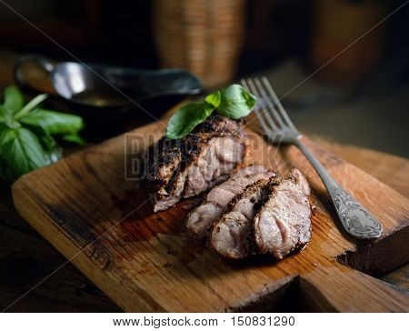 grilled meat, basil, fork on a cutting board on a wooden background