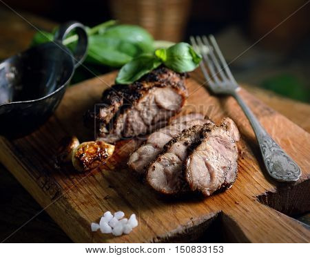 grilled meat, basil, fork and saucers on a cutting board on a wooden background