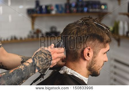 tattooed hands of a barber with clipper and client