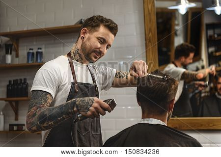 I love my work, smiling hairdresser working with electric clipper
