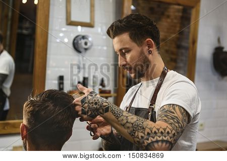professional hairstylist combing hairs of a guy, haircare concept