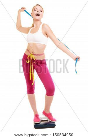 Slimming and weight loss. Happy joyful young woman girl measuring with tape measures on weighing scale. Healthy lifestyle concept. Isolated on white.