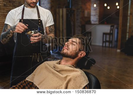 barber preparing to shave his male customer, concept of shaving