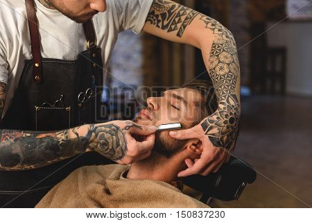 selective focus on barber shaving customer, concept of shaving