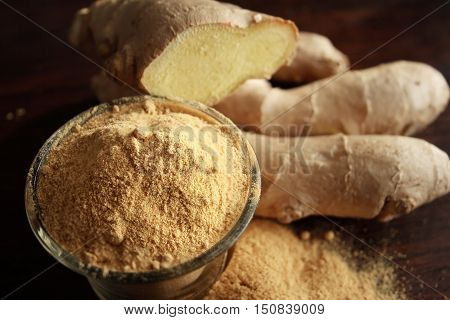 Fresh ginger root and ground ginger spice on wooden background