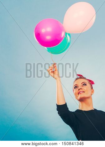 Joy fun and freedom concept. Blonde smiling woman with colorful latex balloons flying balls. Retro fashion styled girl portrait.