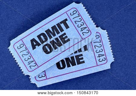 Pair Of Blue Admit One Movie Tickets On A Blue Background.